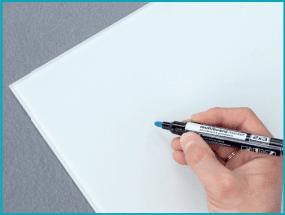 Une main écrit au feutre effaçable à sec ou au feutre craie sur une surface blanche.