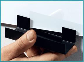 Une main appose un auget noir métal sur un tableau blanc.