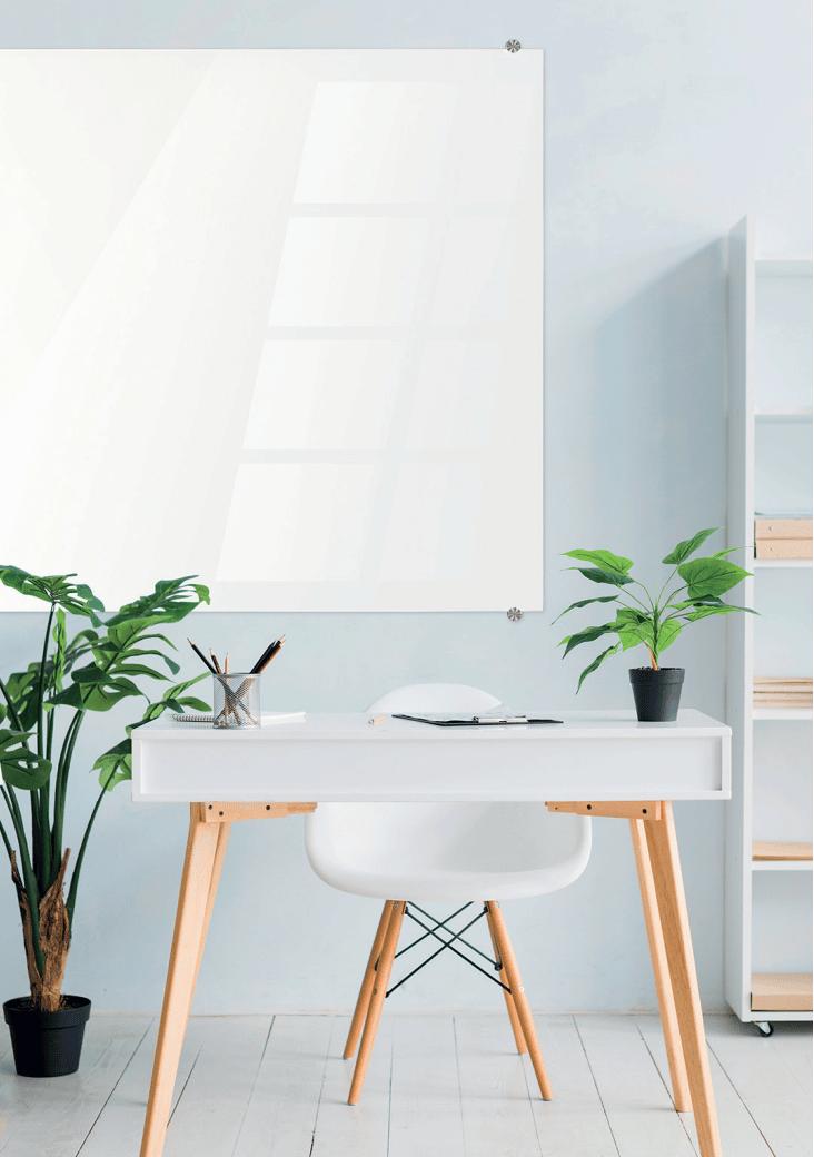 Immense Glass Board disposé derrière un bureau avec des plantes sur le côté