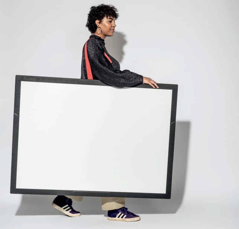 Personne de profil marchant en tenant à son épaule un Flomo Board à surface blanche