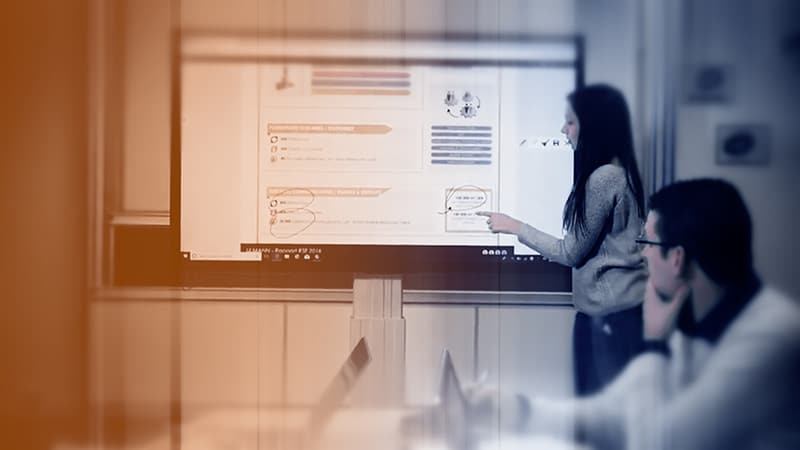 Des salariés sont dans une salle de réunion et regardent leur collègue faire une présentation sur un écran Clevertouch