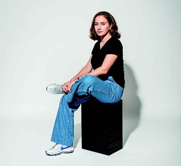 femme assise sur un module X-brick, une jambe remontée sur son genou