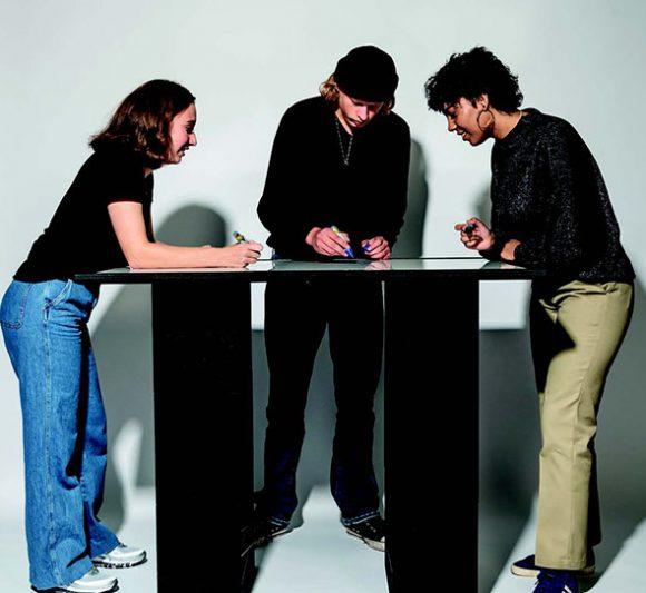 Trois personnes réunies en cession de travail autour d'une série de X-Brick montés en mode bureau